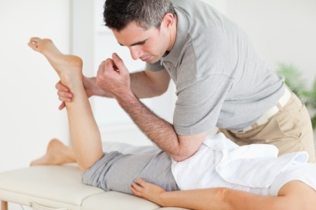 11189798 - a chiropractor stretches a woman's leg in a surgery