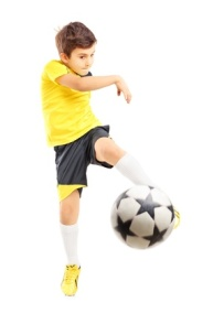 20483849 - full length portrait of a kid in sportswear shooting a soccer ball isolated on white background
