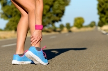 22061319 - sport running ankle sprain. sportswoman touching painful twisted or broken ankle. athlete runner training accident.