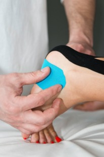 57142773 - therapist positioning kinesio taping on patient's foot