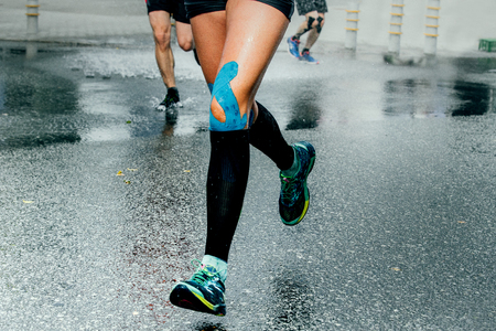61632028 - feet girl runners in compression socks and taping on his knees, running on wet asphalt