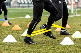 69517030 - thessaloniki, greece - january 14, 2017: the feet of paok players and football training equipment during the training of the team on the pitch toumba.